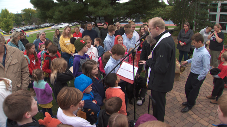 Father Mark Pavlak blesses Jay Mitchell and his dog Hero as Visitation School students look on
