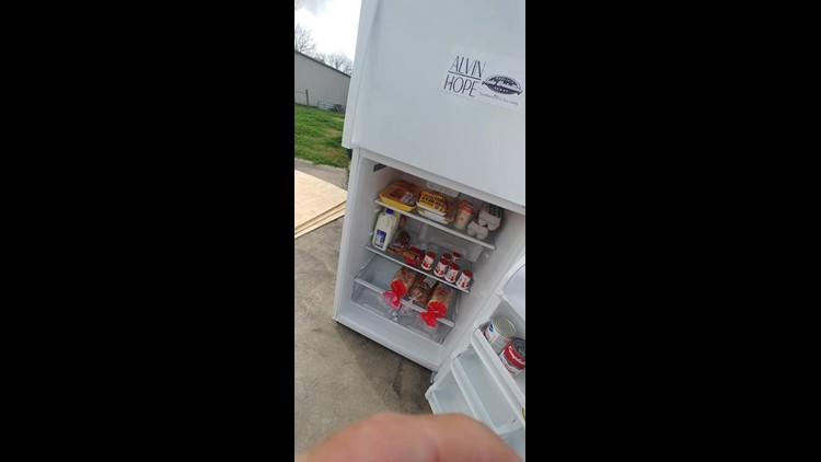 A donated fridge is stocked with donations from the community.