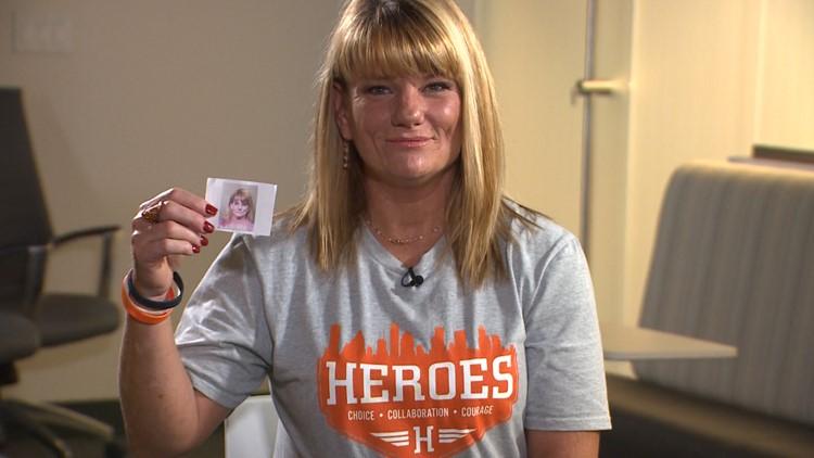 Kelly Kemp holding picture of mugshot