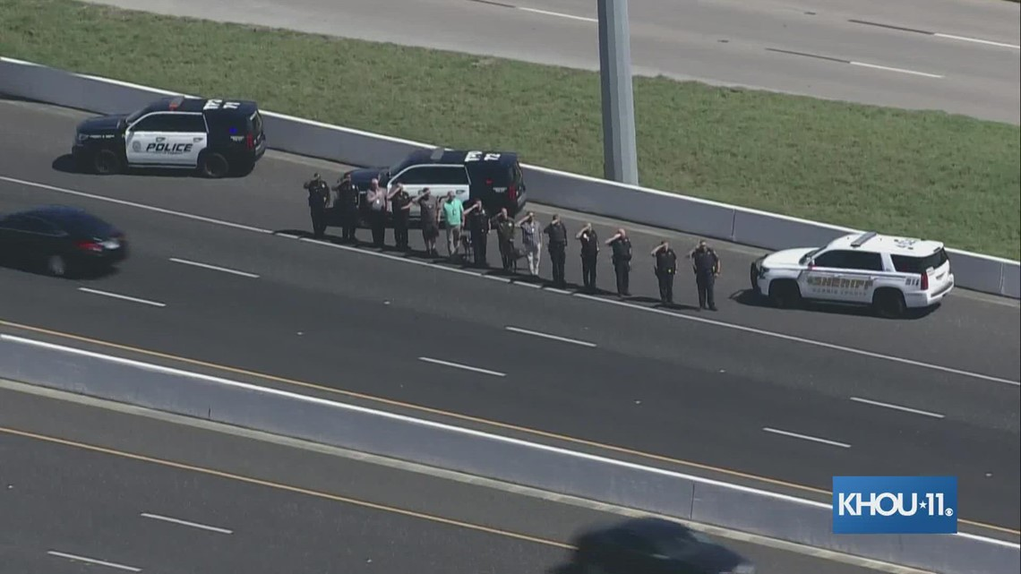 Uniformed officers salute as procession for HPD officer Bill Jeffrey crosses freeway