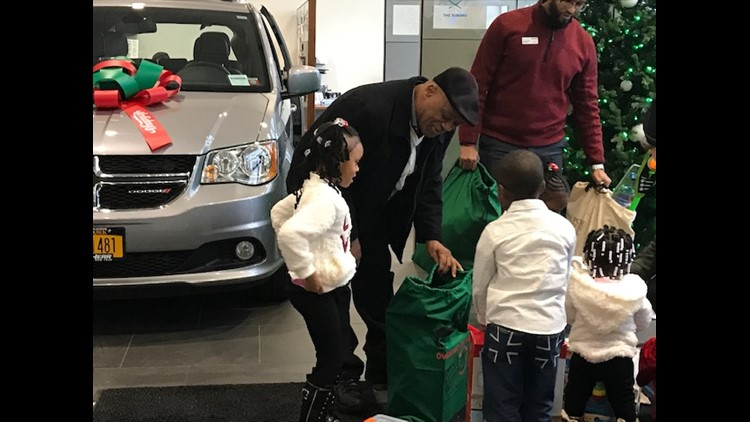 Lamont Thomas opens gifts with kids at West Herr
